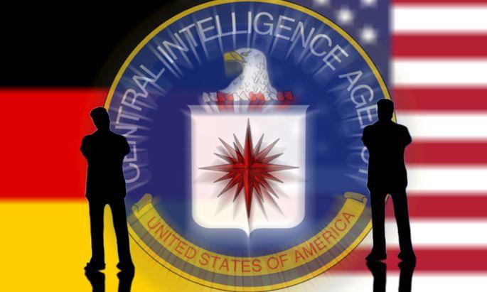 Logo der CIA Central Intelligence Agency mit nachdenklicher Miniatur Figur und Flaggen der USA und B