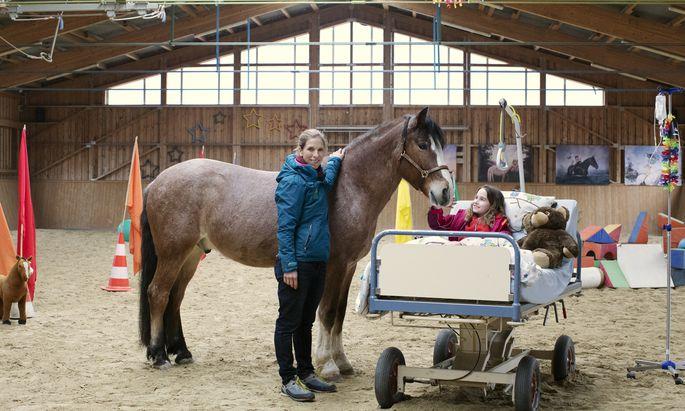 Therapeutin Roswitha Zink mit der neunjährigen Fini, die mit Therapiepferd Kurumi im Krankenbett übt.