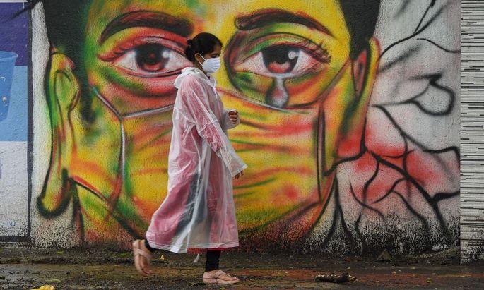Straßenszene mit Wandgemälde in der indischen Metropole Mumbai in Zeiten der Covid-19-Pandemie.