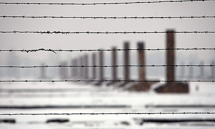 Chimneys are seen through barbed wires during a visit by French secondary school students at the Ausc