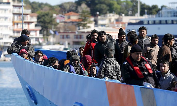 Migrants onboard an EU border agency Frontex boat arrive at the port city of Mytilene on Lesbos island