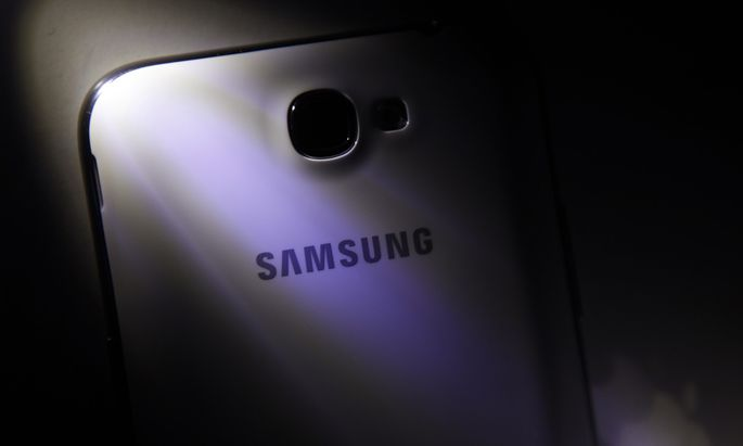 A logo of Apple Inc is reflected next to a Samsung Galaxy Note II smartphone in this photo illustration taken in Beijing