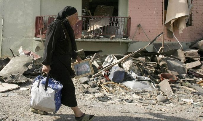 A Georgian woman carries her belongings from her damaged home in Gori