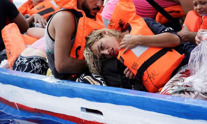 Migrants on a wooden boat wait for the Italian Guardia Costiera in the Mediterranean Sea