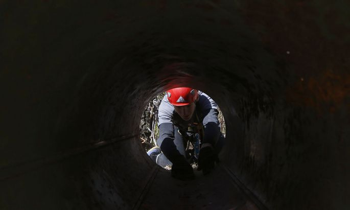 Cave explorer makes his way through a steel tube during an annual international competition for speleologists in Raubichi