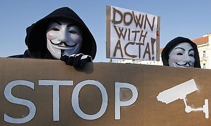 Protesters wearing Guy Fawkes masks hold a banner during a demonstration against the Anti-Counterfeit