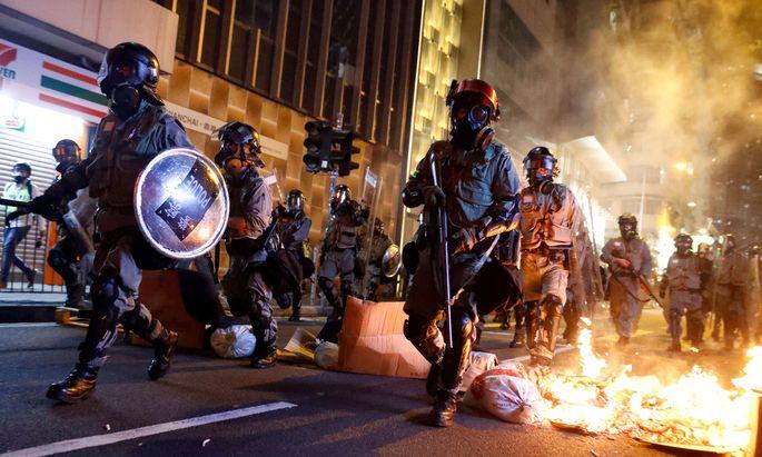 Polizisten durchbrechen in Hongkong eine brennende Barrikade.