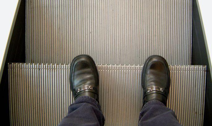 Fuesse auf einer Rolltreppe abwaetrs fahrend