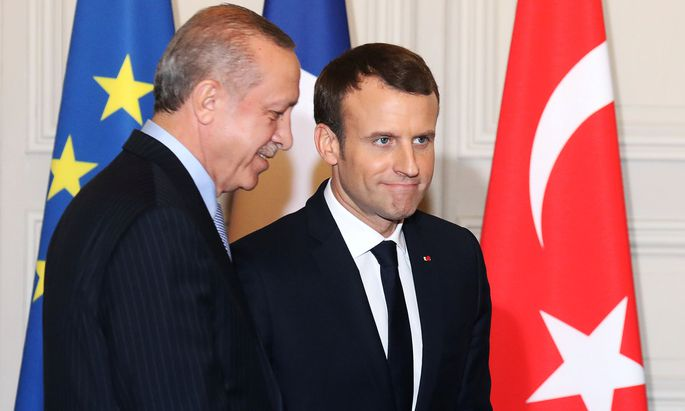 French President Emmanuel Macron and Turkish President Recep Tayyip Erdogan walk out after a joint press conference at the Elysee Palace in Paris