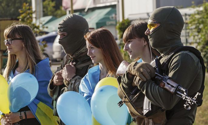 People draped with national flags on their shoulders pose for a photo with armed Ukranian soldiers during a pro-Ukranian meeting in Mariupol