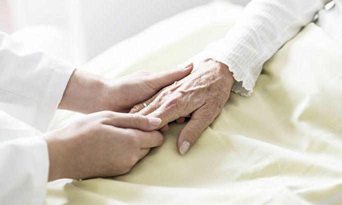 Sinnstiftende Arbeit: eine Pflegerin hält die Hand einer Seniorin.