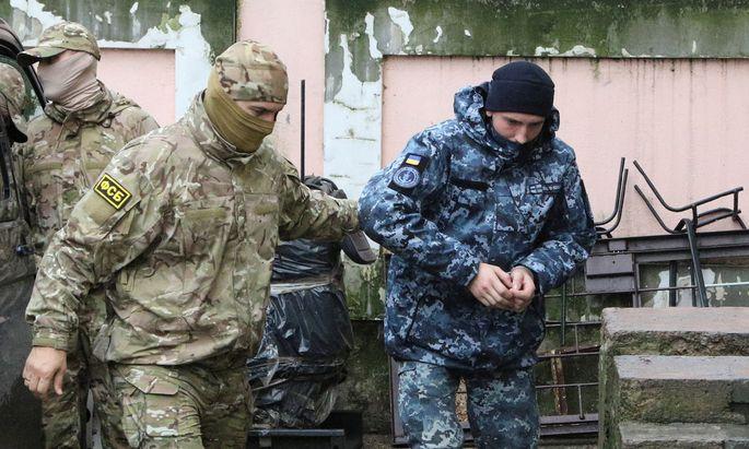 Keine schnelle Freilassung: Ein FSB-Mitarbeiter (links) führt einen ukrainischen Marinesoldaten in das Gerichtsgebäude.