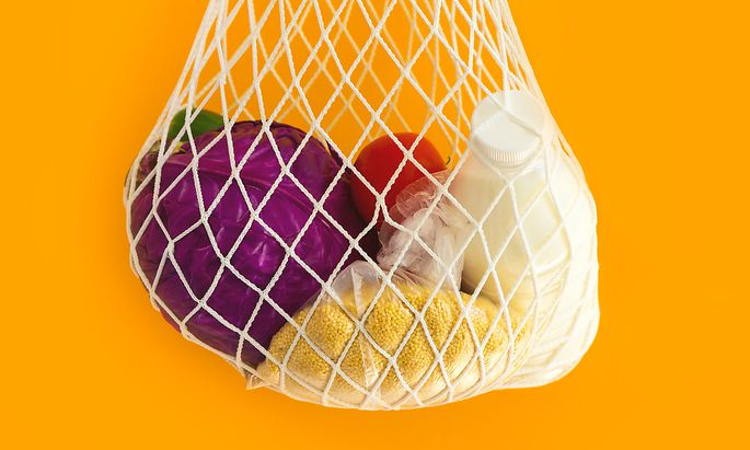 The mesh eco-shopping bag with with cereals, milk and vegetables on a yellow background. The modern reusable purchasing, the concept of zero waste.
