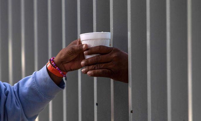 Im mexikanischen Grenzort Tijuana wird ein Kakao durch den Zaun einer Notunterkunft gereicht.