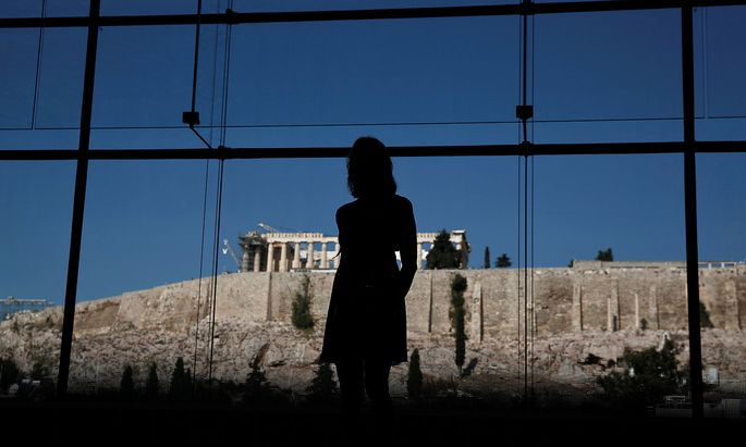 FILE PHOTO: Woman looks at exhibits on display in the Parthenon hall at the Acropolis museum, as the temple of the Parthenon is seen in the background, in Athens