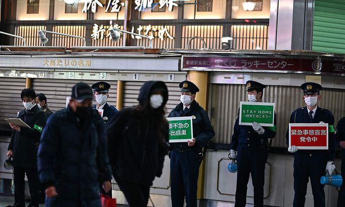 Polizisten weisen in Tokio Passanten darauf hin, wegen der Corona-Pandemie wenn möglich zu Hause zu bleiben.