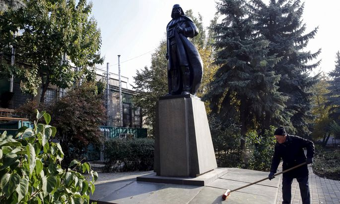 A worker sweeps leaves off a monument to the character Darth Vader from ´Star Wars´, which was rebuilt from a statue of Soviet state founder Vladimir Lenin, in Odessa