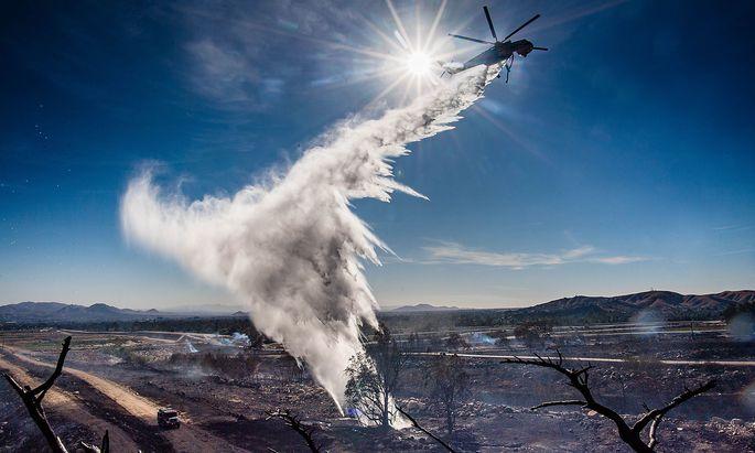 Verbrannte Erde: Ein Löschhelikopter verteilt in der Nähe von San Bernardino Wasser auf ein schwelendes Glutnest.