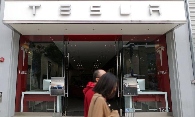 People walk past a Tesla showroom in Santa Monica