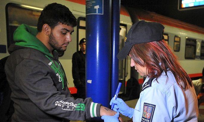 Eine Polizistin schreibt mit Filzstift Nummern auf die Hand eines Flüchtlings.