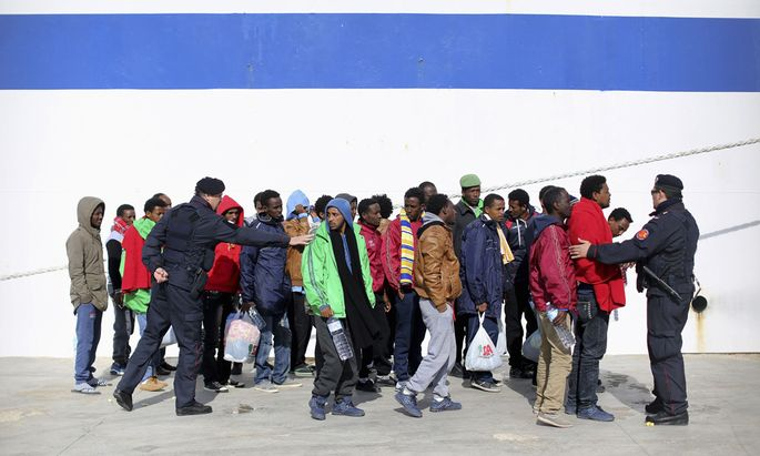 Italian Carabiniere give instructions to migrants as they are transferred to another immigration centre by a ferry boat on Lampedusa