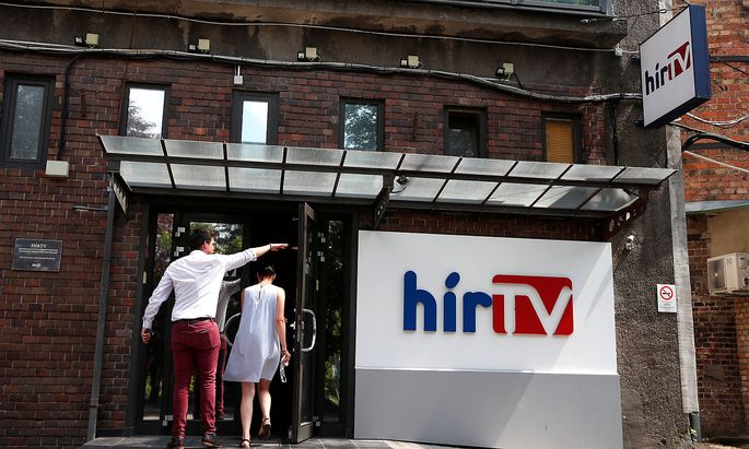 Employees of the Hungarian news television channel, Hir TV, enter the Hir TV headquarters in Budapest