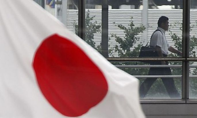 A businessman walks past a Japanese national flag in Tokyo