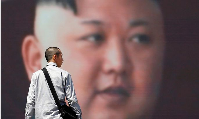 A man walks past a street monitor showing North Korea´s leader Kim Jong Un in a news report about North Korea´s announcement, in Tokyo