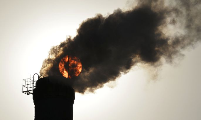 File photo of the sun seen behind smoke billowing from a chimney of a heating plant in Taiyuan