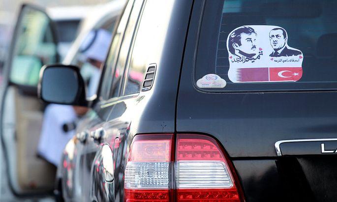 Die Bilder des Emirs von Katar und des Präsidenten der Türkei auf einem Auto in Doha.