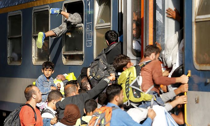 Migrants storm into a train at the Keleti train station in Budapest, Hungary