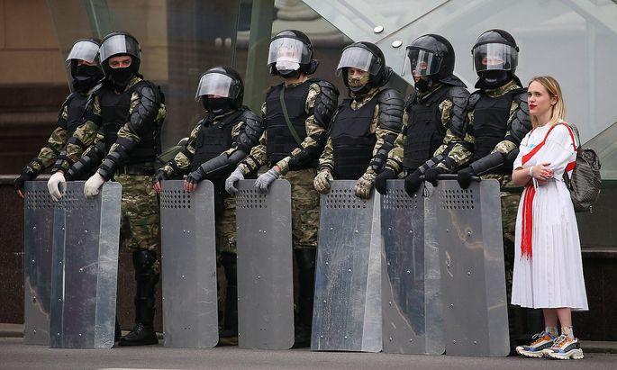 Eine Demonstrantin im September 2020 neben Einsatzkräften in der belarussischen Hauptstadt, Minsk