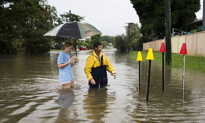 Local resident Paul Shafer and his daughter Lily stand in floodwaters near star pickets that show where the storm water cover has been removed in Hermit Park, Townsville