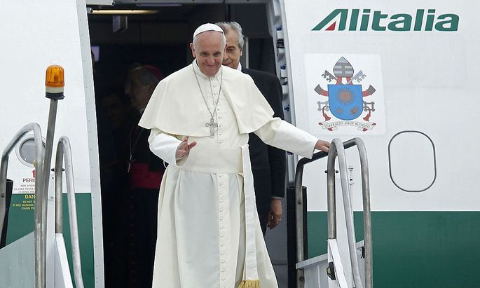 Pope Francis waves upon arrival at Antonio Carlos Jobim International Airport in Rio de Janeiro