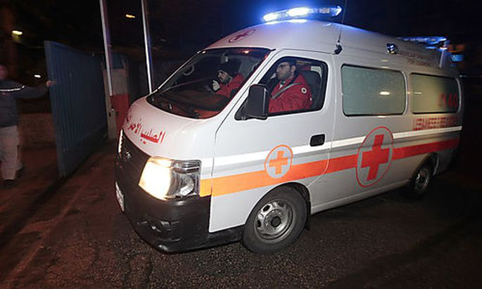 A Lebanese Red Cross ambulance follows Lebanese police vehicles carrying two injured French journalis