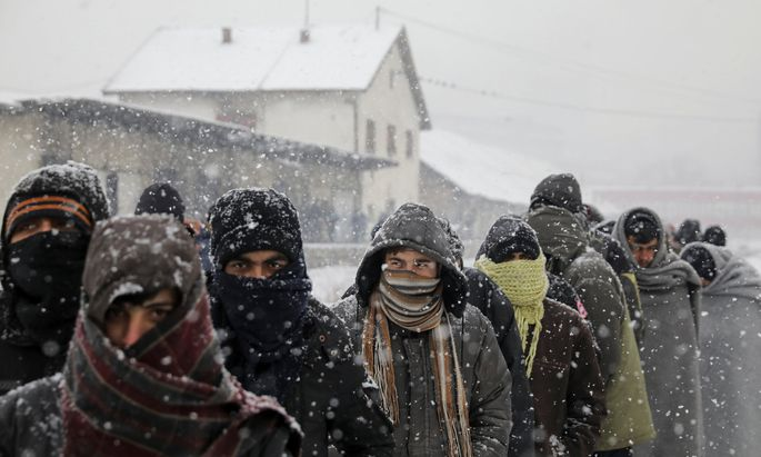 Migrants wait in line to receive free food during a snowfall outside a derelict customs warehouse in Belgrade