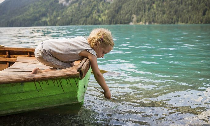 Austria, Carinthia, Weissensee, girl in rowing boat putting a stick in the water