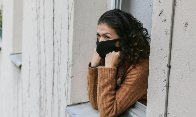frau in quarantaene mit mundschutz schaut depressiv aus dem fenster ihrer wohnung *** woman in quarantine with mouth gua