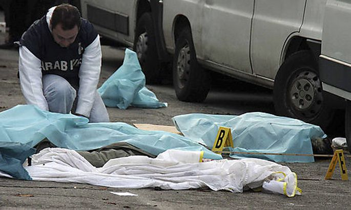 A forensic police officer checks the scene after an Italian man with extreme right-wing views opened