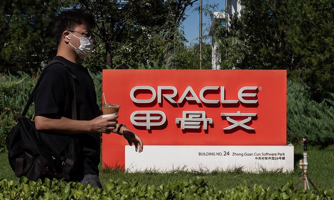 Ein Mann passiert das Firmenschild des Oracle-Office in Peking.
