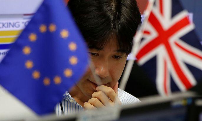 Ein Angestellter einer Bank zwischen der Union Flag und der EU-Flagge.