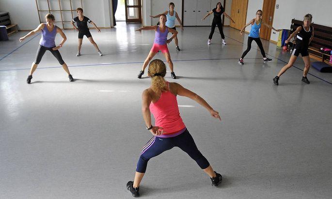 Sportverein beim Training in einer Halle. Einige Frauen turnen.