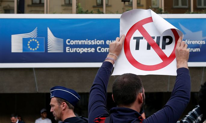 A demonstrator holds a sign during a protest against TTIP in Brussels