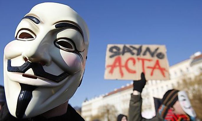 A protester wearing a Guy Fawkes mask attends a demonstration against the Anti-Counterfeiting Trade A