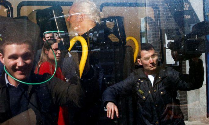 Julian Assange (Mitte) wird in einem Polizeifahrzeug von der Botschaft weggebracht.