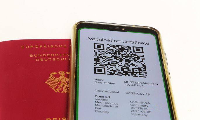 Symbolbild: Reisepass und ein digitaler Gruener Pass als Nachweis einer Impfung *** Symbolic passport and a digital gree