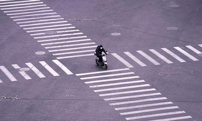 Ein MOpedfahrer mit Schutzmaske in Shanghai