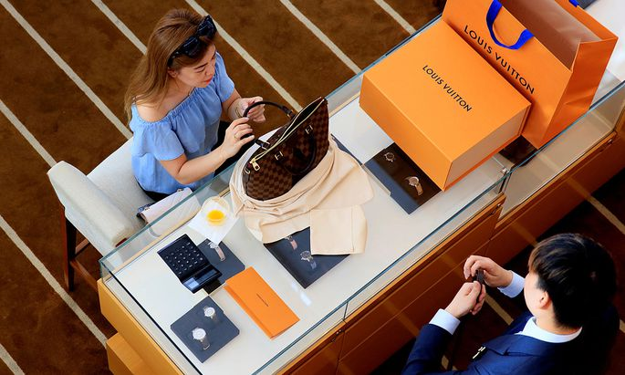 A woman buys a Louis Vuitton bag in a shop in Singapore