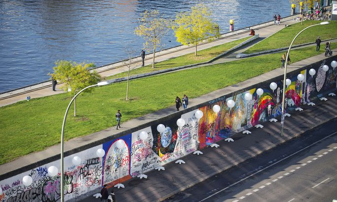 People walk under stands with balloons placed along the former Berlin Wall location at East Side Gallery in Berlin