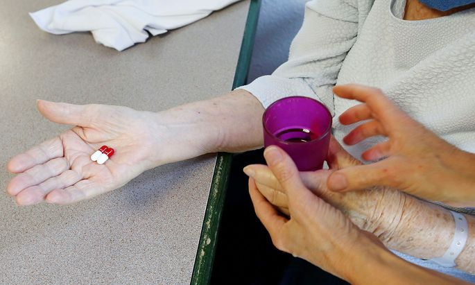 Eine Frau bekommt von einer Pflegerin Tabletten in einem Altersheim. (Symbolbild